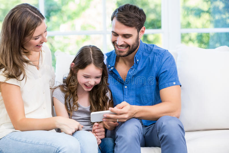 Famille regardant le téléphone intelligent tout en se reposant sur le sofa photo libre de droits