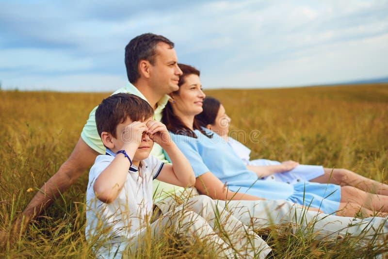 Famille reposant se reposer ensemble sur l'herbe en nature image libre de droits