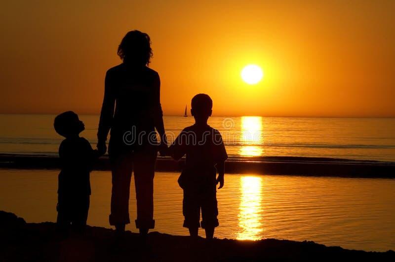Famille restant à la plage images libres de droits