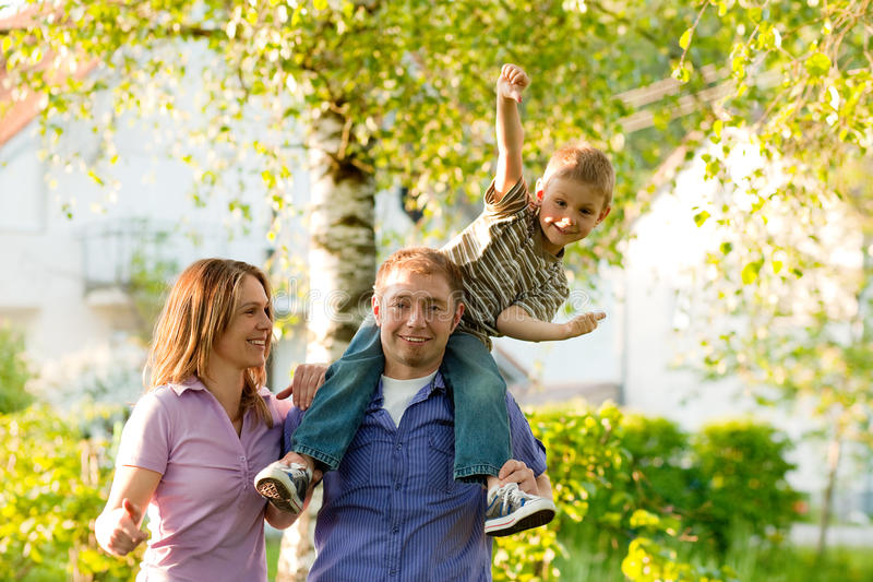 Famille restant devant des maisons image stock
