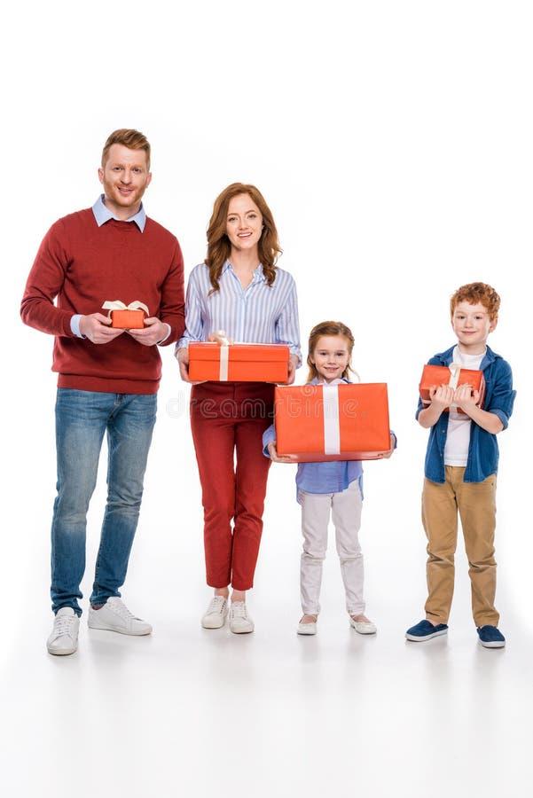 famille rousse heureuse tenant des boîte-cadeau et souriant à l'appareil-photo images stock