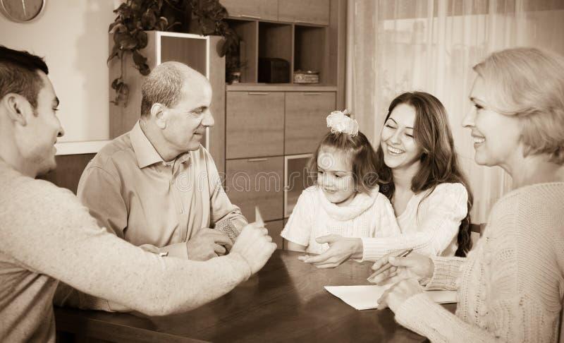 Famille s'asseyant à la table avec des cartes images stock