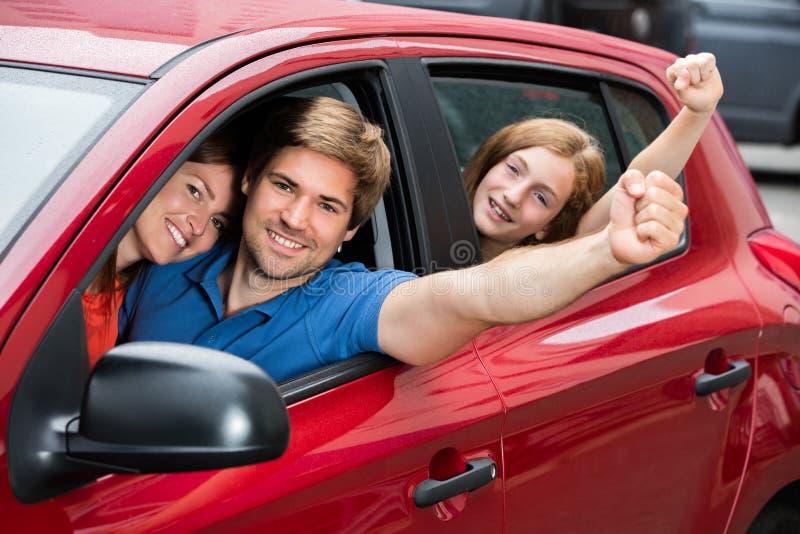 Famille s'asseyant dans la voiture soulevant leurs bras images libres de droits