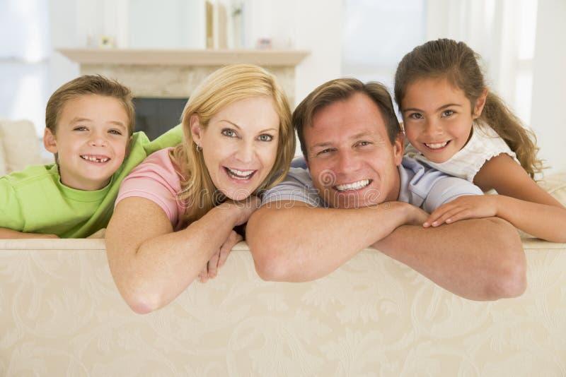 Famille s'asseyant dans le sourire de salle de séjour photos libres de droits