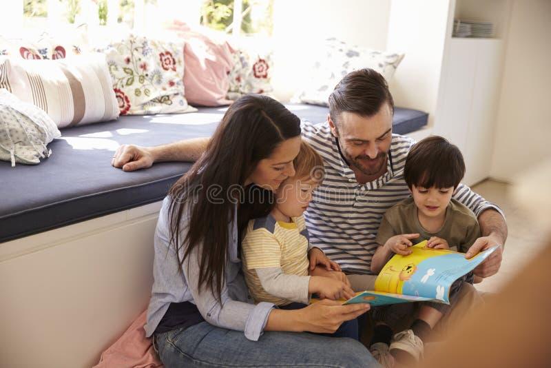 Famille s'asseyant sur l'histoire de lecture de plancher à la maison ensemble photographie stock