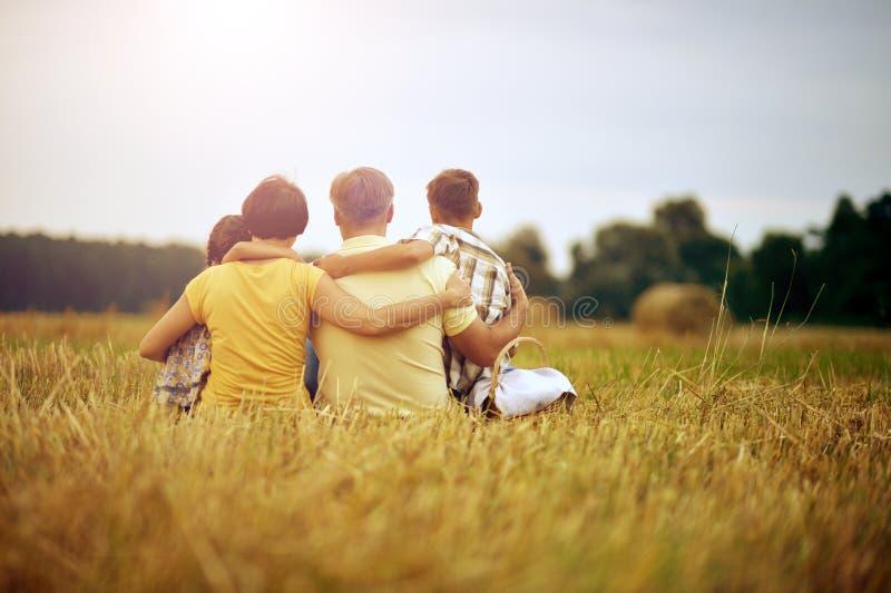Famille s'asseyant sur le champ de blé dans le jour ensoleillé image stock