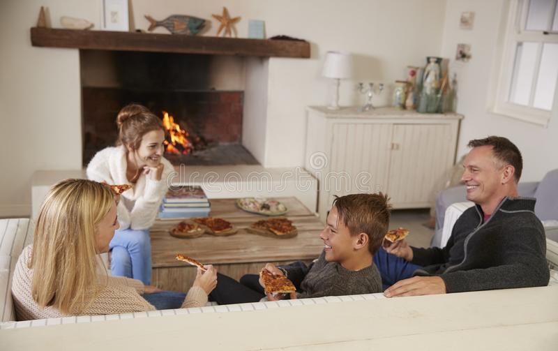 Famille s'asseyant sur le feu ouvert de Sofa In Lounge Next To mangeant de la pizza photos stock