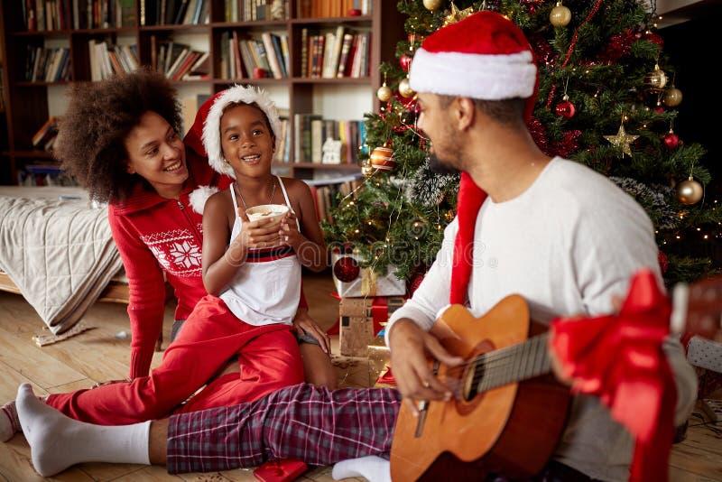 Famille s'asseyant sur le plancher ensemble et les chansons de écoute de guitare à h image libre de droits