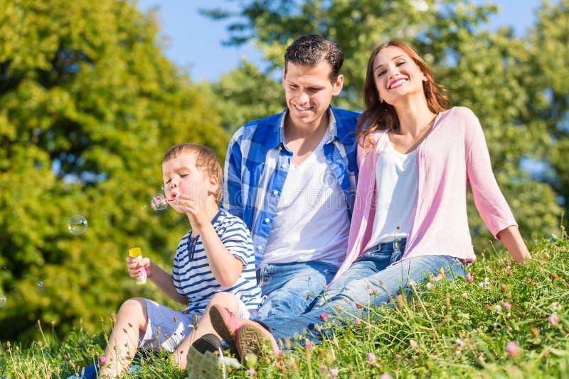 Famille s'asseyant sur le pré jouant avec des bulles de savon image libre de droits