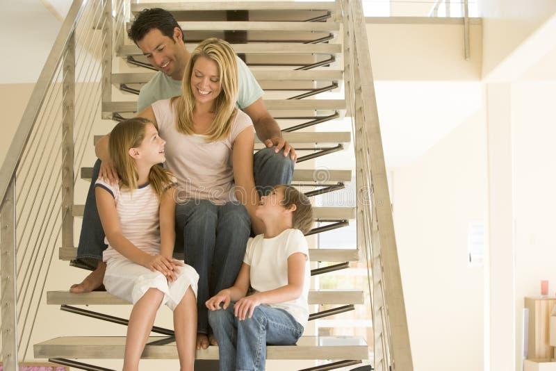 Famille s'asseyant sur le sourire d'escalier photo stock