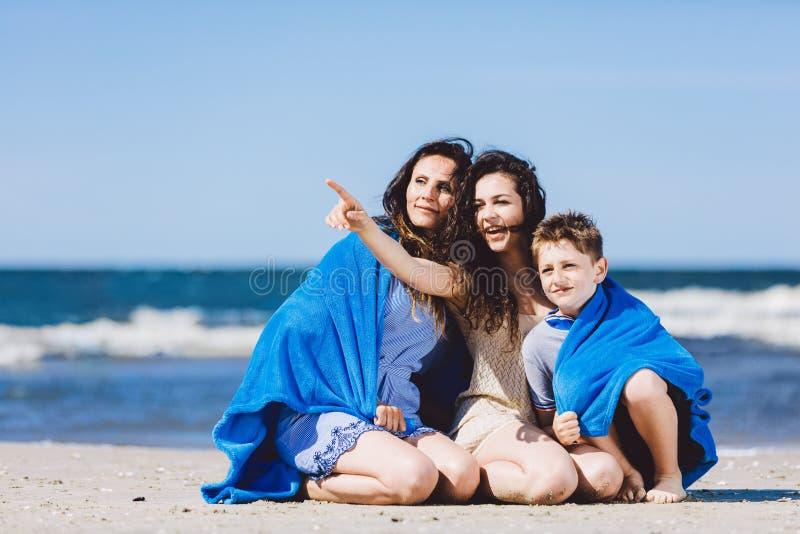 Famille s'asseyant sur une plage, une soeur plus âgée dirigeant son doigt photographie stock libre de droits