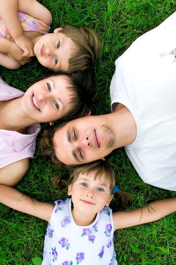 Famille se trouvant sur l'herbe photographie stock libre de droits