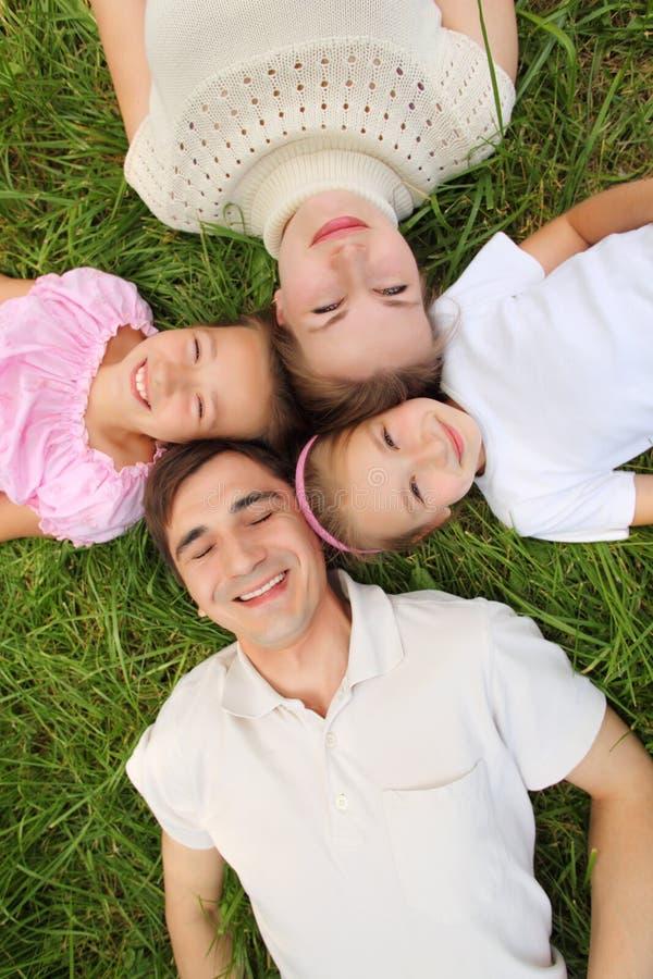 Famille se trouvant sur l'herbe, vue à partir de dessus photographie stock libre de droits