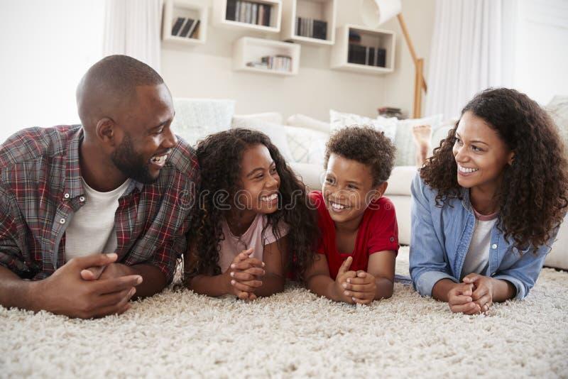Famille se trouvant sur la couverture dans le salon à la maison photo stock