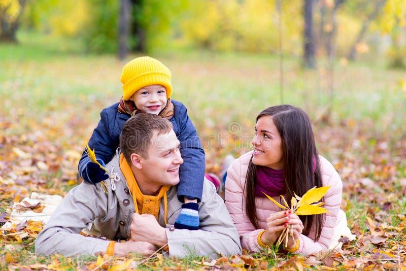 Famille se trouvant sur le parc d'automne de feuilles photographie stock libre de droits