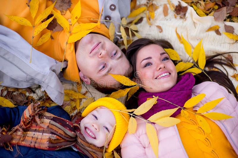 Famille se trouvant sur le parc d'automne de feuilles photos libres de droits
