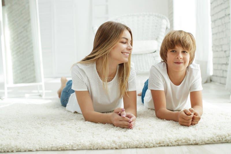 Famille se trouvant sur le tapis à la maison photo stock