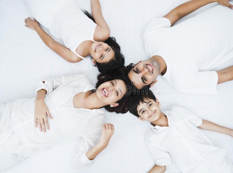 Famille se trouvant sur un lit photo stock