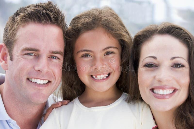 Famille souriant à l'extérieur photo stock