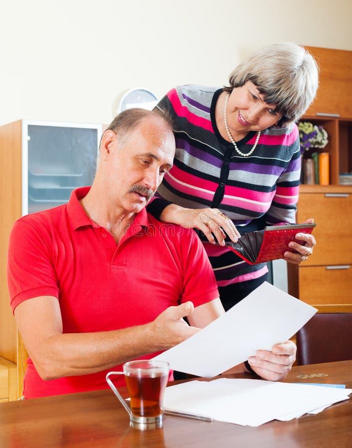Famille supérieure avec les documents financiers image stock
