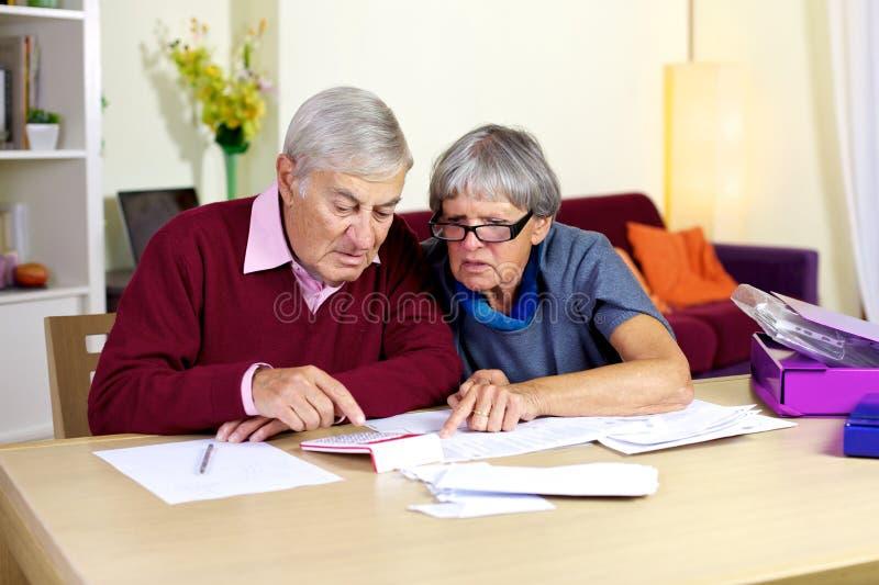 Famille supérieure essayant de faire des comptes financiers sur des factures images libres de droits