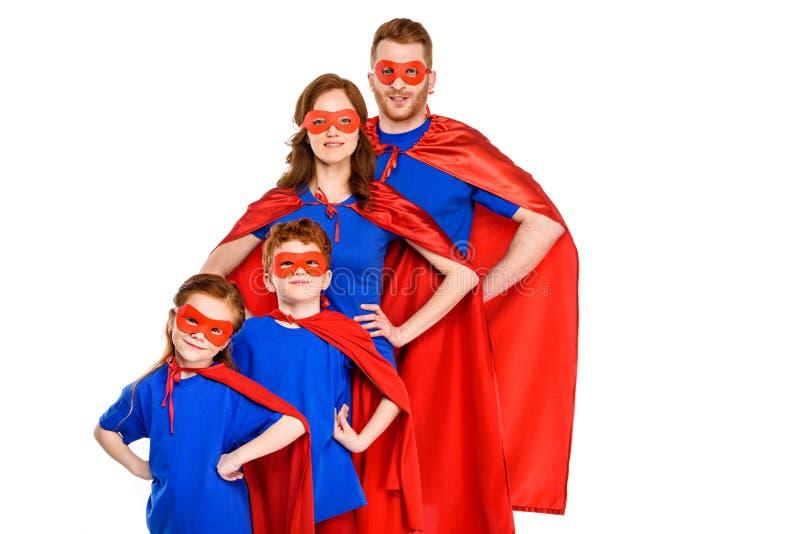 famille superbe sûre dans les masques et des manteaux se tenant avec des mains sur la taille et souriant à l'appareil-photo photos stock