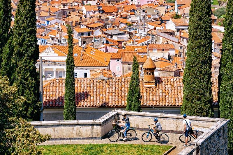 Famille sur des bicyclettes à de vieux toits de ville de Piran en Slovénie photographie stock