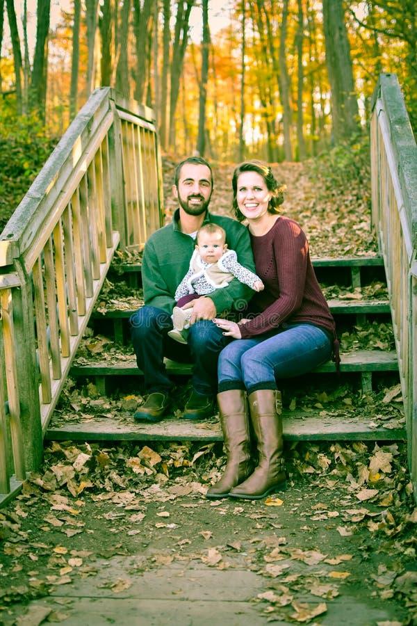 Famille sur des escaliers couverts de feuilles d'automne photos stock