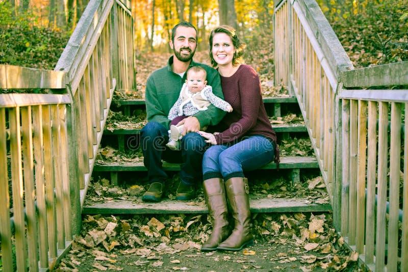 Famille sur des escaliers couverts de feuilles d'automne image stock
