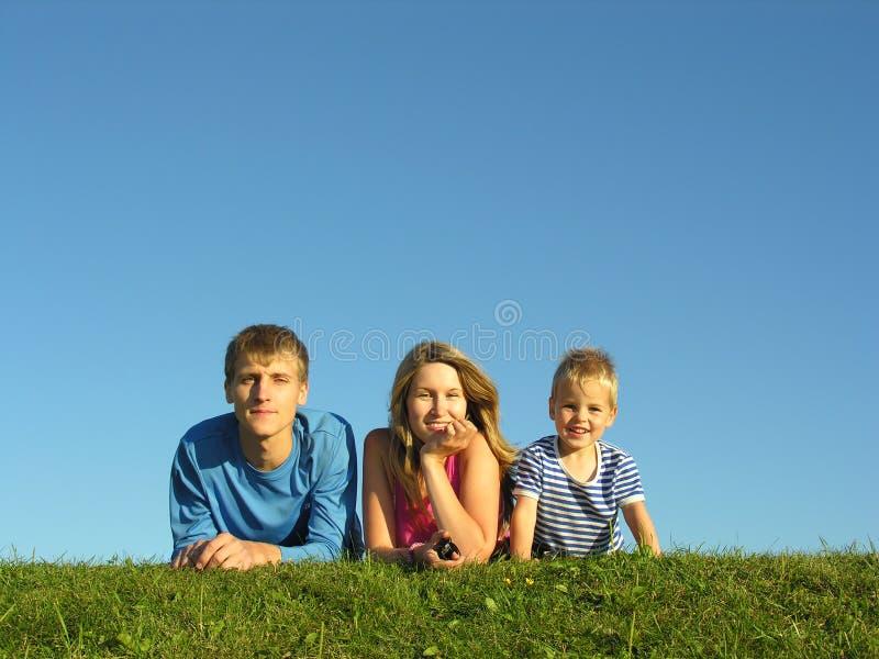 Famille sur l'herbe sous le ciel bleu photos libres de droits