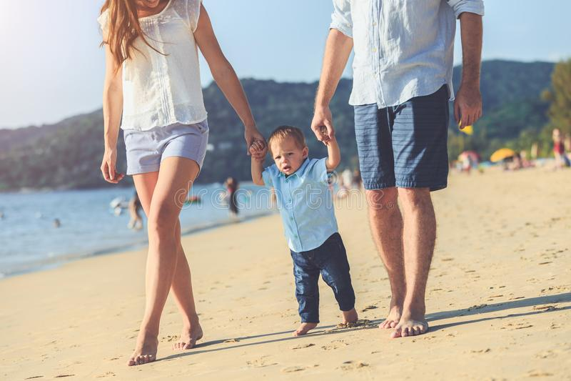 Famille sur la plage, mère tenant la main de son fils et marche, images libres de droits
