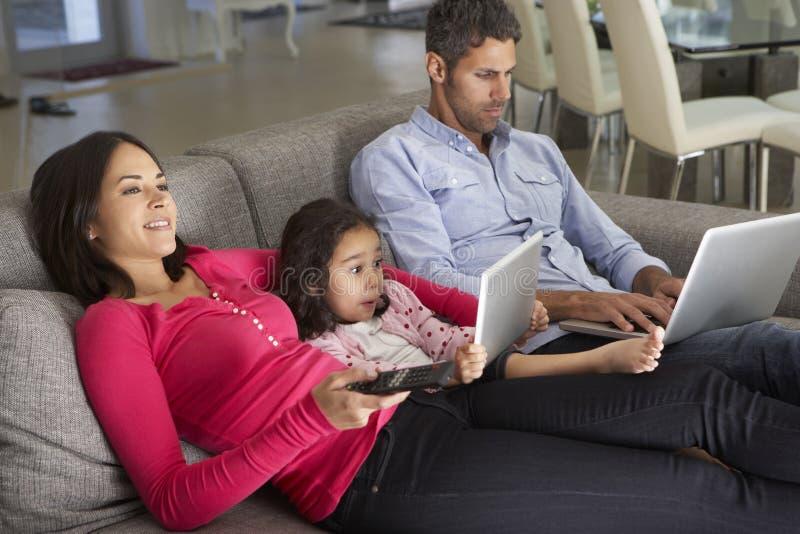 Famille sur la Tablette de Sofa With Laptop And Digital regardant la TV images libres de droits