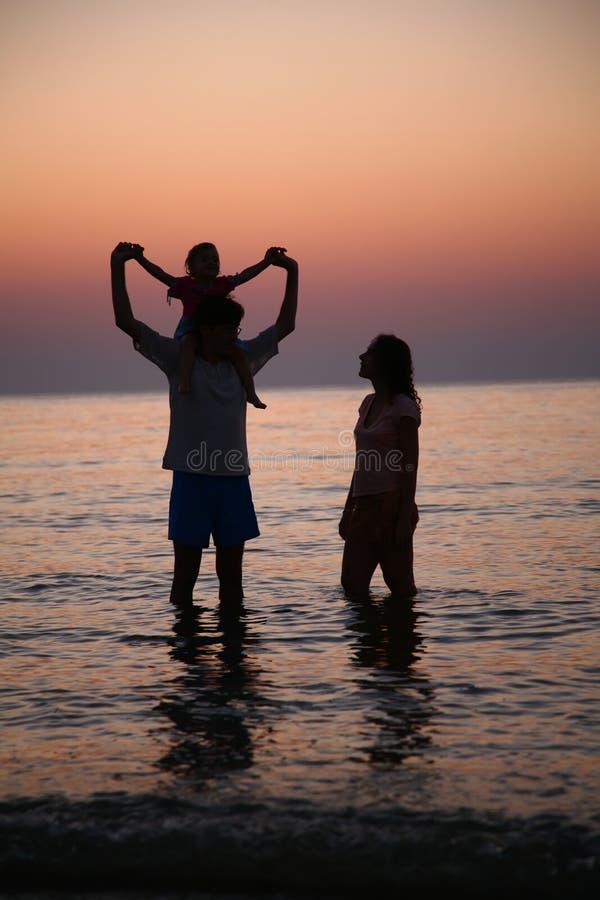 Famille sur le coucher du soleil photo stock