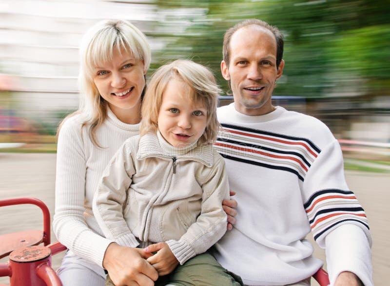 Famille sur le rond point de rotation photographie stock
