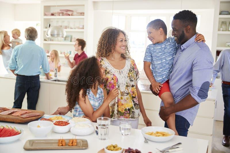 Famille sur plusieurs générations et amis se réunissant dans la cuisine pour la partie de célébration photo libre de droits