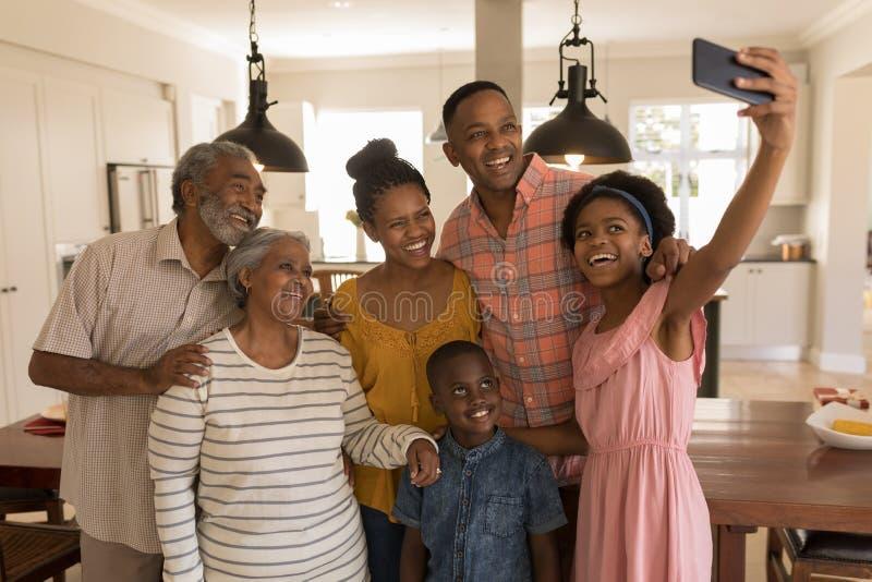 Famille sur plusieurs générations prenant le selfie avec le téléphone portable à la maison photo stock