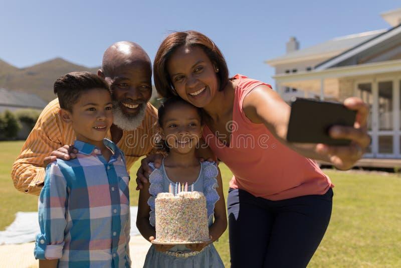 Famille sur plusieurs générations prenant le selfie avec le téléphone portable tout en célébrant l'anniversaire du grandaughter photographie stock libre de droits