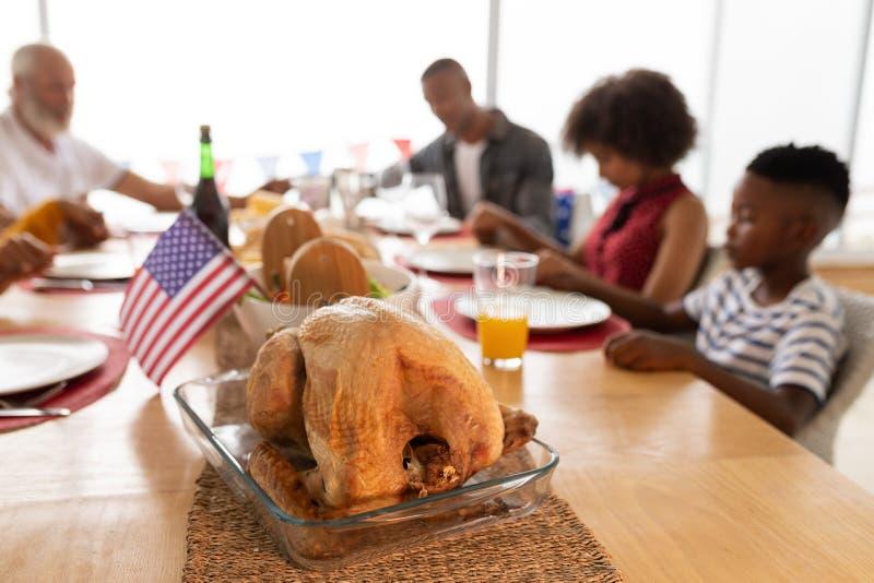 Famille sur plusieurs générations priant avant d'avoir le repas sur la table de salle à manger images libres de droits