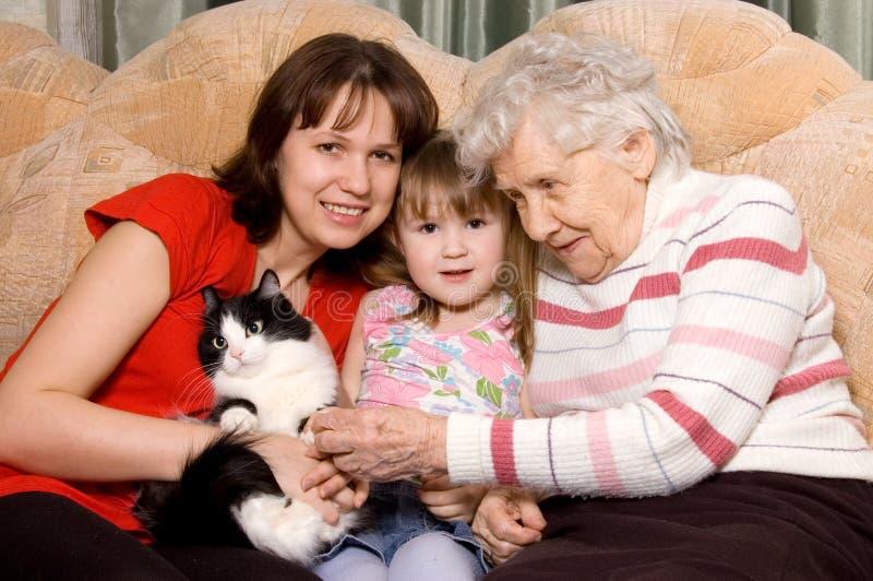Famille sur un sofa avec un chat photo libre de droits