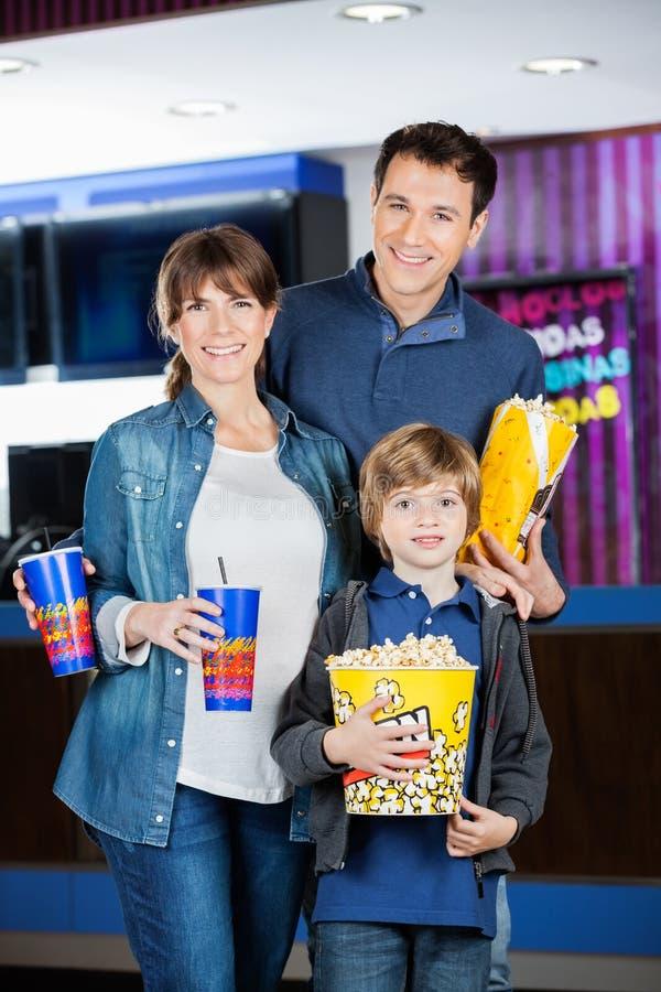 Famille tenant des maïs éclatés et des boissons au cinéma images libres de droits