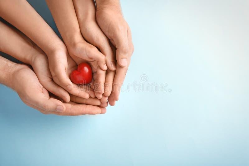 Famille tenant le petit coeur rouge dans des mains photographie stock libre de droits