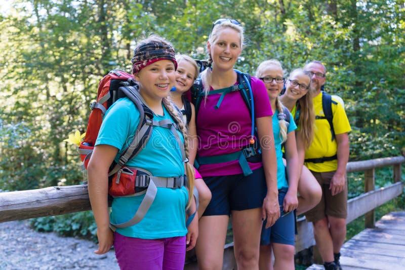 Famille trimardant dans la forêt se tenant sur peu de pont images stock