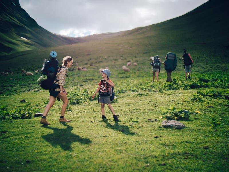 Famille trimardant dans les montagnes Une jeune mère heureuse et son fils prennent une hausse ensemble dans les montagnes sur un  photographie stock libre de droits