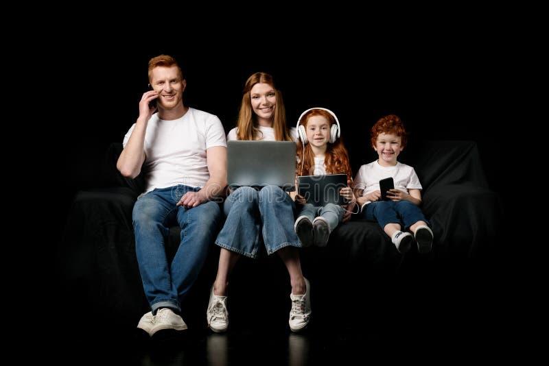 Famille utilisant de divers dispositifs numériques images stock