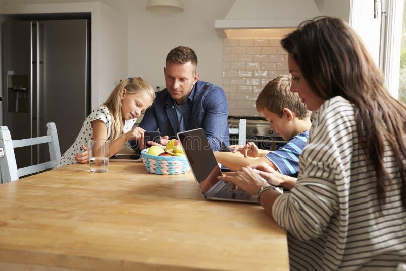Famille utilisant des dispositifs de Digital à la table de cuisine photos stock
