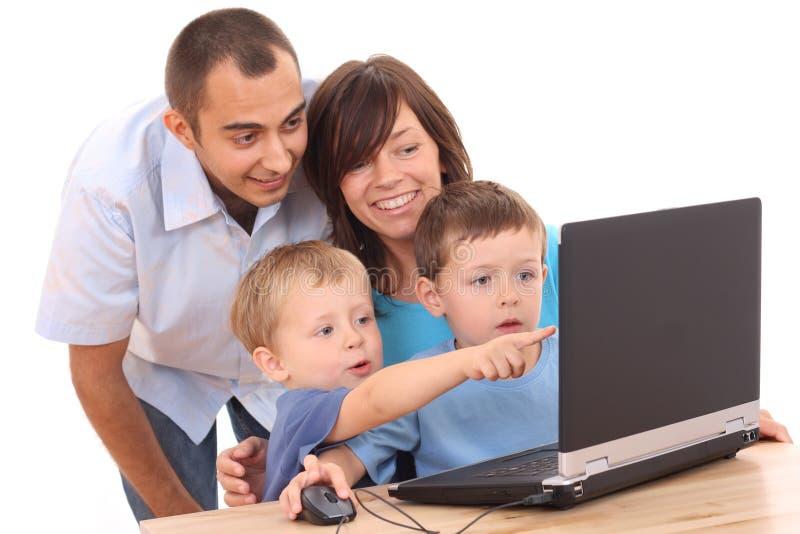 Famille utilisant l'ordinateur portatif photos libres de droits