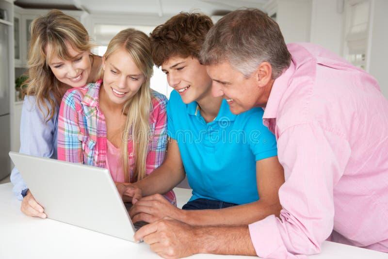 Famille utilisant l'ordinateur portatif sur la table photos libres de droits