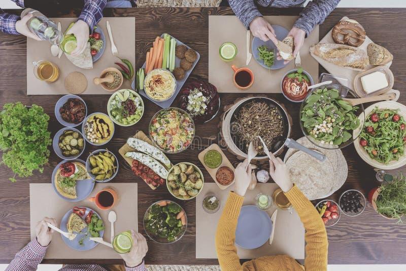 Famille végétarienne mangeant le dîner sain image stock