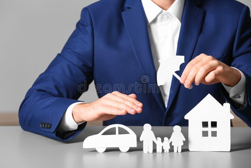Famille, voiture et maison masculines de papier de bâche d'agent d'assurance photographie stock libre de droits