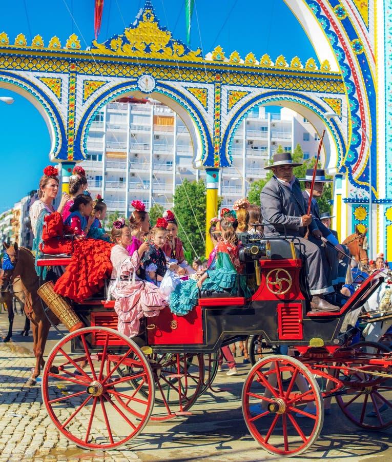 Familles espagnoles dans la robe traditionnelle et colorée voyageant dans chariots hippomobiles chez April Fair, foire de Séville photo stock